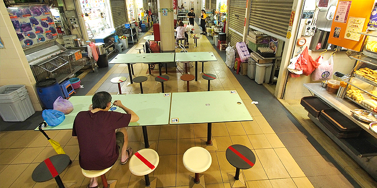 A food court marks seats to be left empty to ensure safe distancing between customers. Photo credit: ADB.