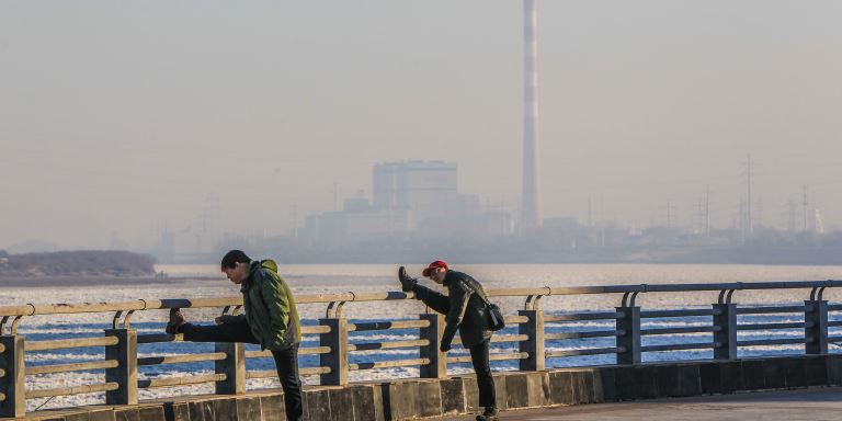 Men exercising against the backdrop of an industrial development in the PRC. Photo credit: ADB.