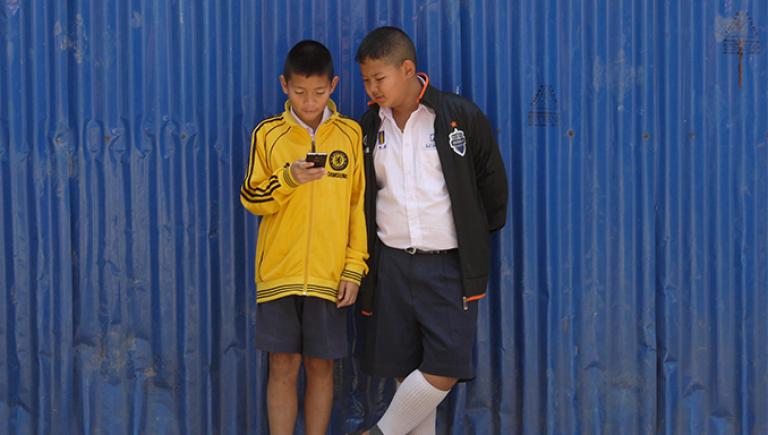 School kids access a smartphone while waiting for class to start. Photo credit: ADB