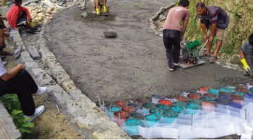 Plastic cells made from plastic waste are filled with concrete and compacted by a plate vibrator to build roads. Photo credit: ADB.