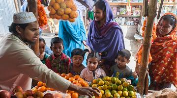 Mothers and their children shop at a fresh food market in the Bhashantek area of Dhaka city in Bangladesh, using money distributed through cash-based transfers. Photo credit: World Food Programme/Wahid Adnan.
