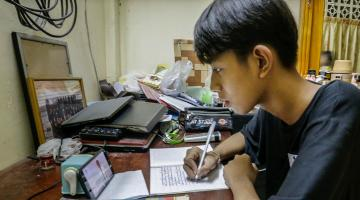 A student in Cambodia joins an online class on a mobile phone. Photo credit: ADB.
