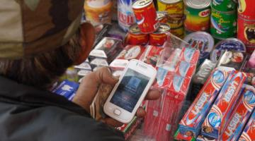 A merchant uses a smartphone to send money abroad. With mobile remittance solutions, many South Asians, particularly those from the rural areas, will be able to gain access to formal financial channels. Photo credit: Lester Ledesma/ADB.
