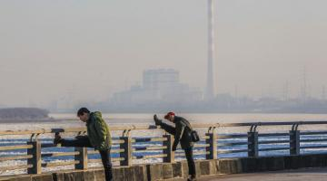 Men exercising against the backdrop of an industrial development in the People's Republic of China. Photo credit: ADB.