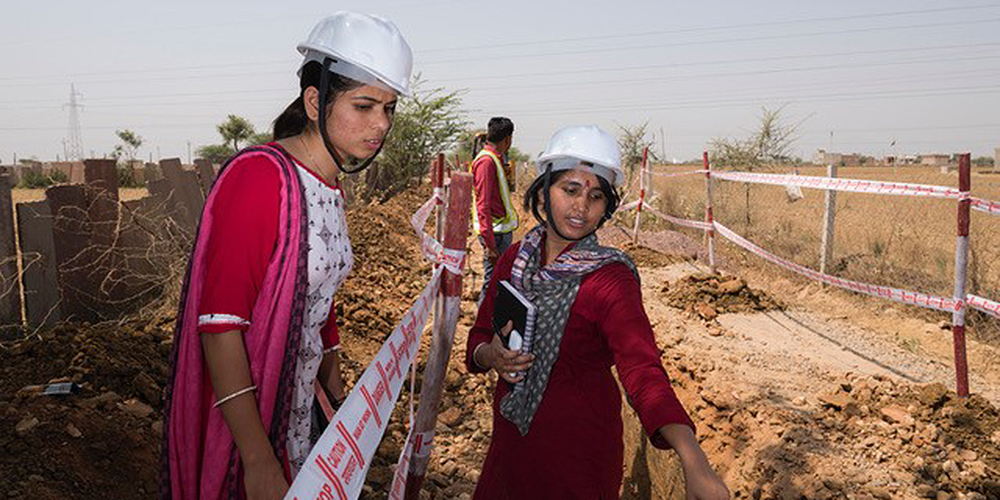 Junior engineers Neelam Meena (left) and Nisha Beniwal (right) check on the progress of trenches being dug for a new sewer line. Female engineering students are offered internships to diversify the state's workforce. Photo credit: Amit Verma, ADB.