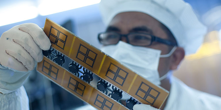 A student examines a printed circuit board at a polytechnic in Indonesia. Photo credit: ADB.